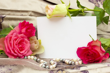 anniversary flower: roses with pearls strand and blank card background
