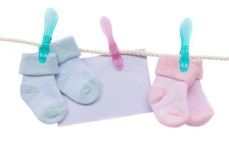 bébé bleu et chaussettes roses avec une enveloppe blanche suspendue à la corde sur fond blanc