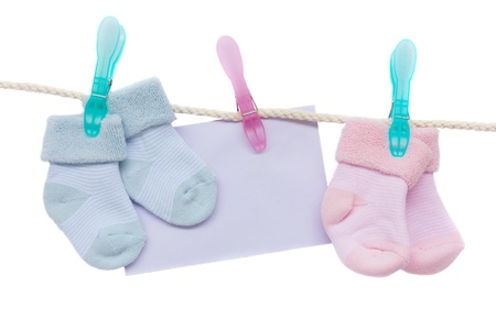 baby blue and pink socks with blank envelope hanging on rope on white photo