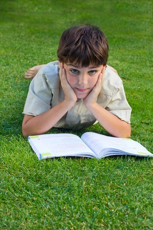 boy  reading book on green grass lawn photo