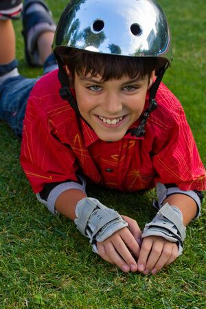 happy boy in roller blades grear laying on grass photo
