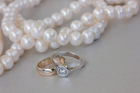 engagement rings with pearls  strand on gray background photo