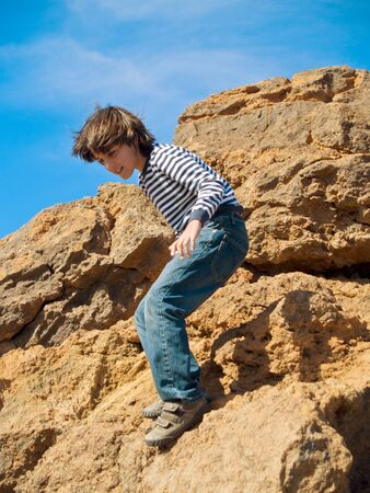 caucasian boy finding path in mountain rocks photo