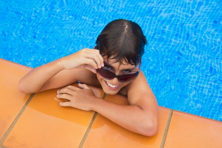 beautiful teenage boy looking above sunglasses and smiling in pool photo