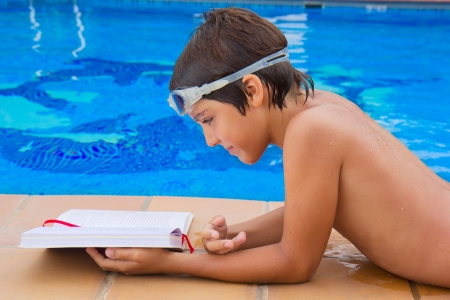 handsome boy reading book near blue  pool photo