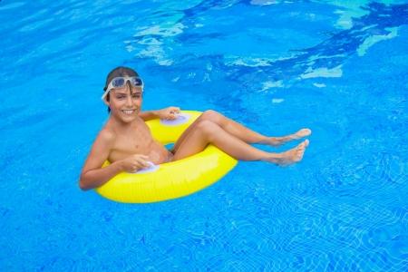 sunbath: knappe jongen die zonnebaden in het zwembad op rubberen ring