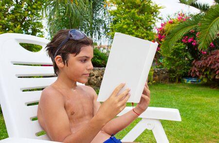 handsome boy reading book near  pool lawn photo