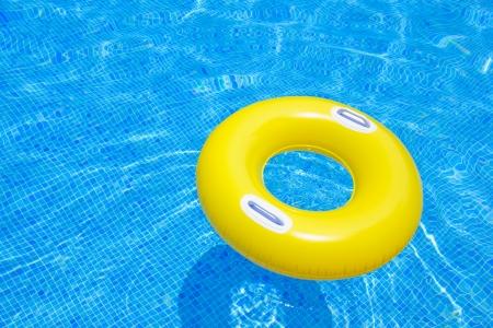anillo de goma flotando en la piscina de azulejos azules transparentes Foto de archivo