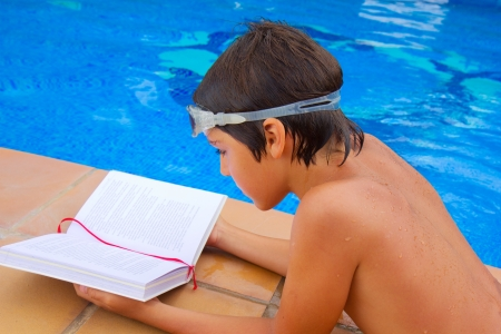 kid reading book near blue  pool in summer day photo