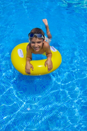 boy swimming in pool on rubber ring photo