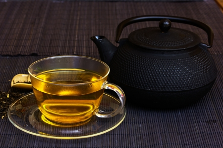 cup of tea and teapot on bamboo mat photo