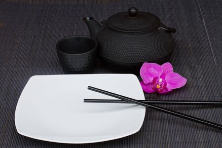 asian food concept - empty plate with chopsticks and tea set photo