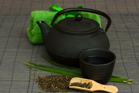 asian tea set with raw tea and towels photo