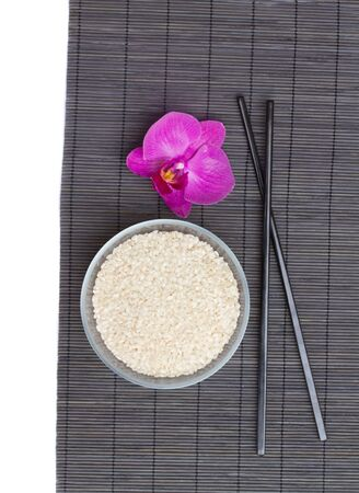 plate with rice and black chopsticks isolated on white photo