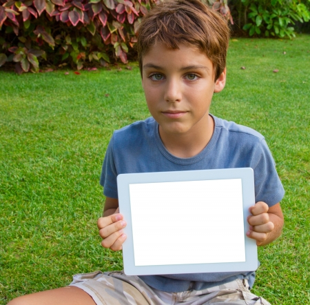 e pretty: boy  showing tablet  PC on green grass lawn with copy space