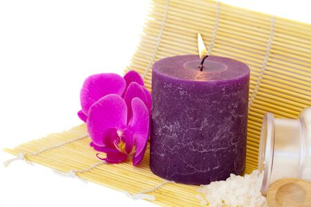 candle on mat with sea salt and flowers isolated on white  photo