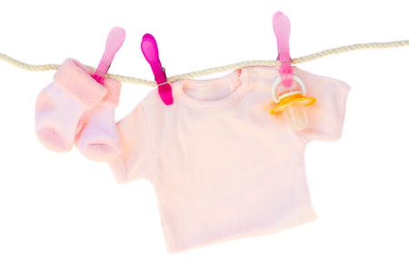 baby pink clothes hanging on rope on white background photo
