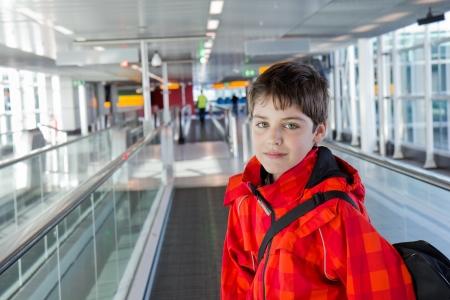 Chłopiec w nowoczesnej hali lotniska patrząc cieśninę