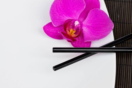 asian food concept - empty plate with chopsticks photo