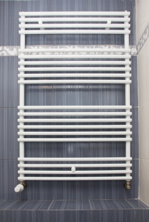 Modern new white big radiator with thermostat photo