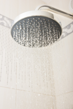 shower head: shower head with  drops and streams of water - concept for domestic water usage  Stock Photo