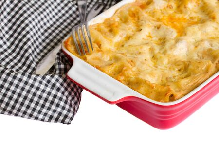 close up of lasagna on table with fork and knife isolated on white photo