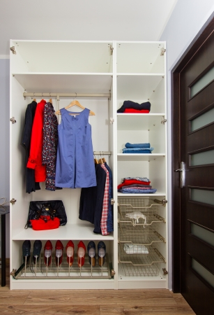 white modern wardrobe withfemale red and blue  closing Stock Photo