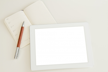blank tablet pc with open notebook and pen photo