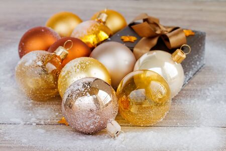 golden christmas decorations and gift box on wooden background photo