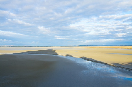 Mont Saint Michel shadow  over sand, France photo