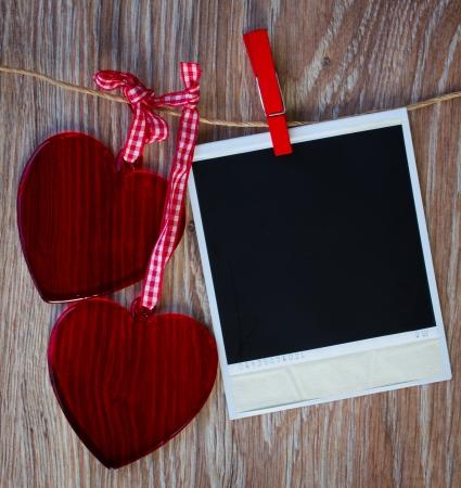 saint valentin coeur: Blank photo instantan�e et de deux coeurs en verre rouges suspendus sur la corde � linge, fond grunge sombre Banque d'images