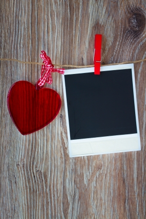 color photo: Blank instant photo and  red glass heart hanging on the clothesline, dark grunge background  Stock Photo