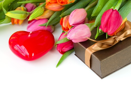 tulips with gift box and heart candle on white table photo
