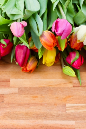 multocolored spring tulips laying on wooden table photo