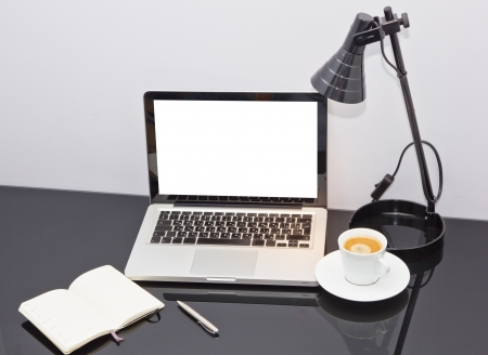 Still-life of computer, pen, coffee mug on table  and lamp photo