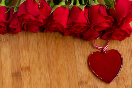 valentines day mother s: roses with glass red  heart candle on wooden  table Stock Photo