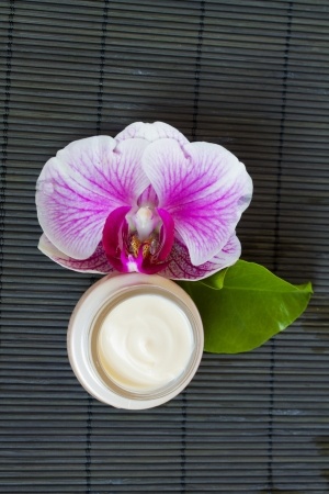 orchid flower and jar of cream photo