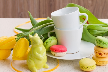 easter breakfast with coffee, rabbit, fresh tulips and macaroons photo