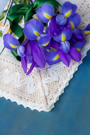 bouquet of iris flowers laying on blue  table photo