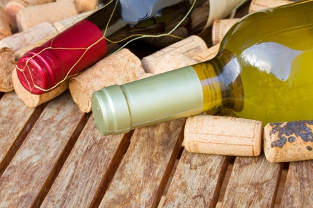 red and white wine bottles with corks on wooden table photo