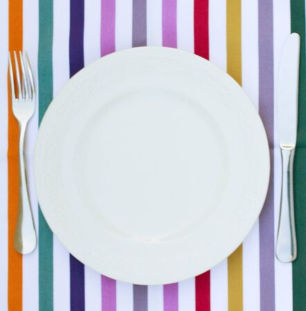 empty white plate with knife and fork on tablecloth photo
