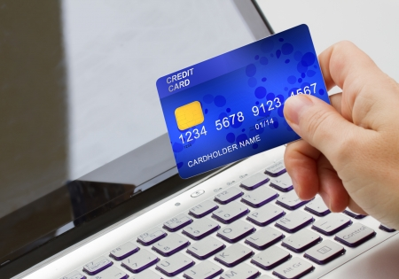 trade credit: hand holding plastic card  on open notebook background