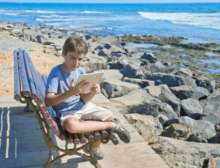 tween boy: boy  holding  and looking at  tablet PC by the sea side Stock Photo