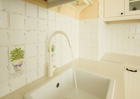 close up of sink with running water in white  kitchen in antique rustique style photo