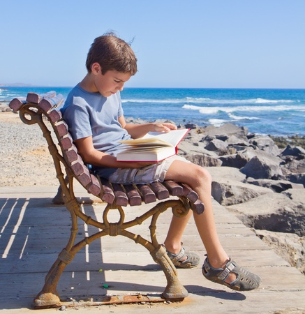 boy  reading book on summer bench on sea coast photo