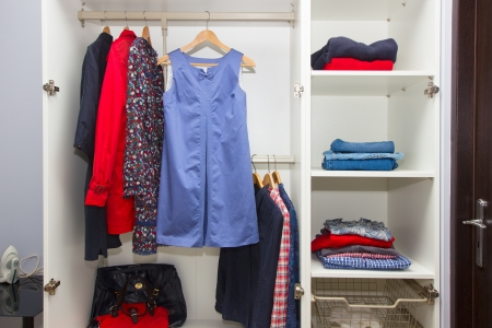 white modern wardrobe withfemale red and blue  closing photo