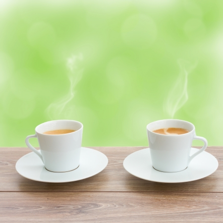 two coffee cups in garden on wooden table photo
