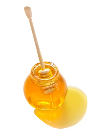 glass pot  full of honey and stick isolated on white background Stock Photo - 18558509