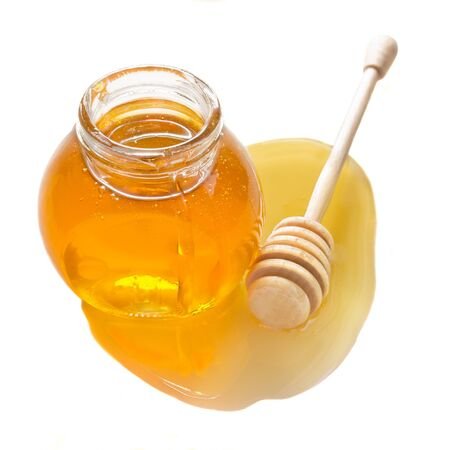 jar full of honey and stick isolated on white background  photo