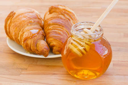 breafast with croissants and honey on wooden table photo